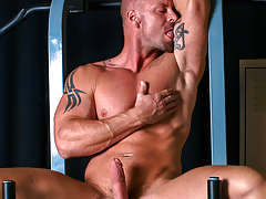Mitch tugs on his cock, buck naked on his workout machine